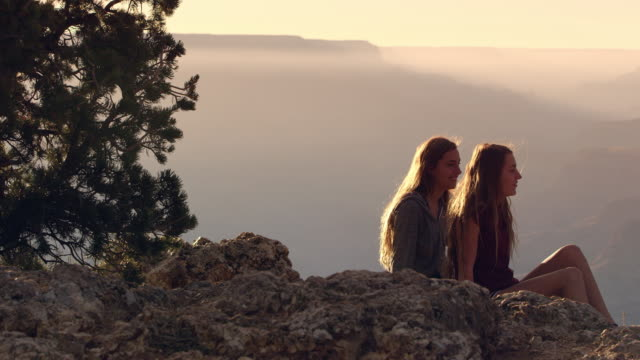 Panning view of two teenage girls on cliff at Grand Canyon