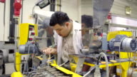 panning: young and big engineer rake plastic in hopper on extruder machine