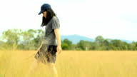 panning: young woman carefully walk  on Savannah field