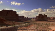 Panoramic view of Arches National Park with tourist cars driving in distance