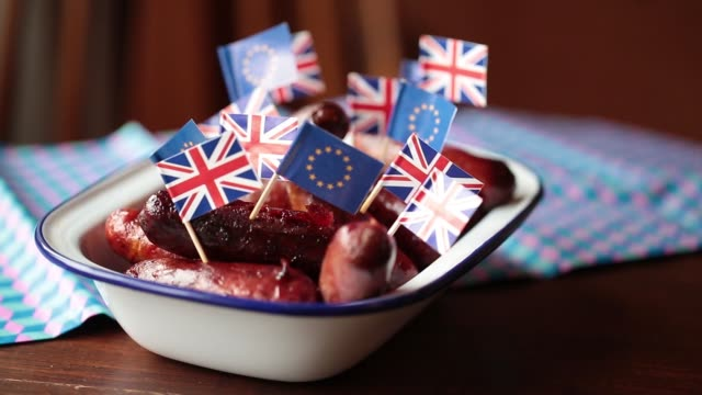 Pans and pull focus of British Union Flags commonly known as Union Jacks and European Union EU flags standing on cocktail sticks from dish of...