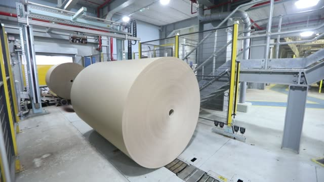 Paper rolls move along conveyor belts in the machine house at the Townsend Hook paper mill operated by Smurfit Kappa Group Plc near Maidstone UK on...