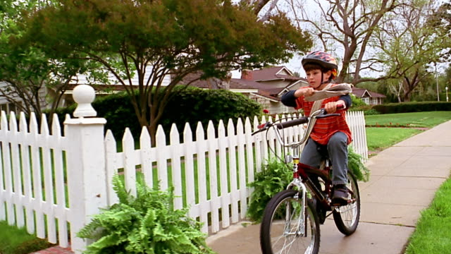 A paperboy riding a bike tosses a newspaper over a white-picket fence..