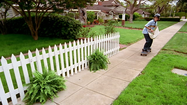 A  paperboy riding a skateboard tosses a newspaper over a white-picket fence.