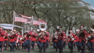 Parade featuring police officers riding bikes bands playing musical instruments little league players women waving American Flags and Uncle Sam /...