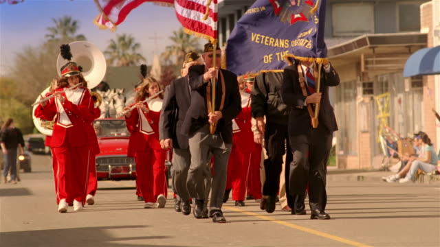 Parade led by war veterans and followed by high school marching band proceeding down street with spectators waving and applauding from sidelines / California
