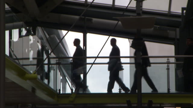 A parade of professionals in suits walks through an open upper passage in an Antwerp courthouse.