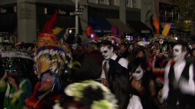 Parade participants show off their costumes and dance down the parade route to live music
