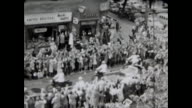 Parade through West Berlin privately filmed from a balcony many motorcycle policemen passing then the open car with John F Kennedy as president of...