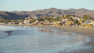 Paradise tropical beach. San Juan del Sur establishing shot / b-roll. Only few people in a calm orange light sunset of this Latin America town. Fishers arrive to the coast. Local restaurants with palm roof on the background.