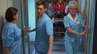 DS Paramedics bringing an injured female into the ER through a hospital hallway