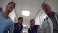 Paramedics, doctor and nurse walking on a corridor with a patient