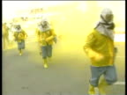 Paramedics in yellow protective suits run with stretcher during security drill in preparation for chemical attack South Korea 16 Mar 98