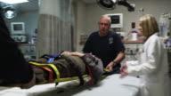 MS Paramedics placing patient on hospital bed / Payson, Utah, USA