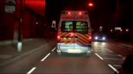 Paramedics working overnight in Birmingham City Centre DRIVER'S POINT OF VIEW following ambulance along road / patient being wheeled out of ambulance...