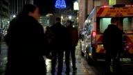 Paramedics working overnight in Birmingham City Centre People along street past ambulance / people outside pub or bar / ambulance along street with...