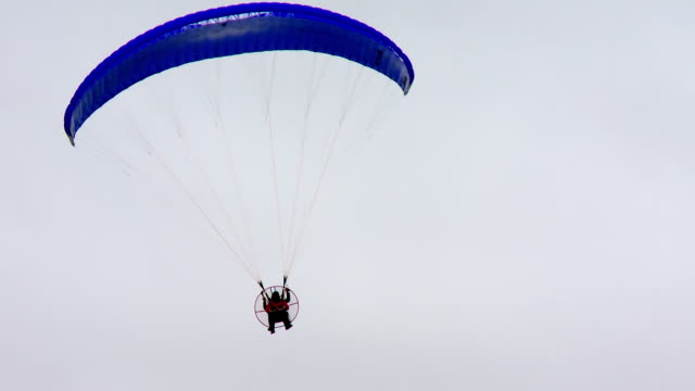 A paramotor flying in a cloudy sky