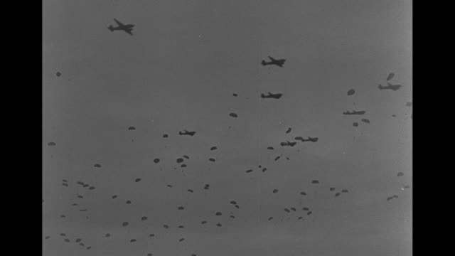 VS paratroopers floating to earth / Allied Forces leaders Bernard Montgomery Dwight Eisenhower Arthur Tedder face left / hundreds of parachutes in...