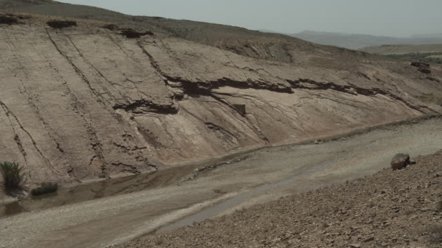 A parched riverbed surrounded by an impressive hillside landscape.