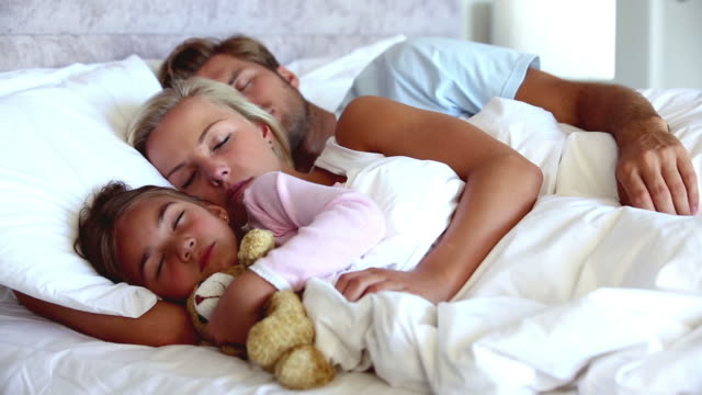 Parents and daughter holding teddy bear sleeping - Schlafzimmer bild a ber bett ...