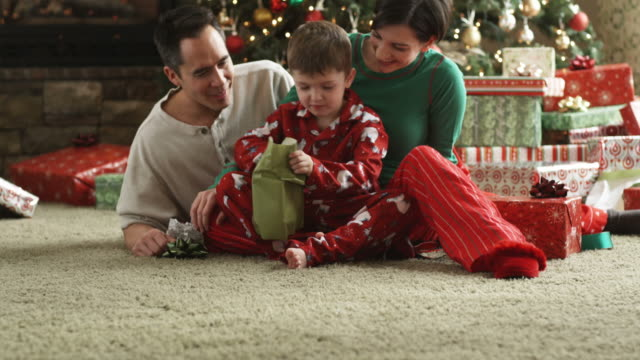 parents and little boy opening a Christmas present