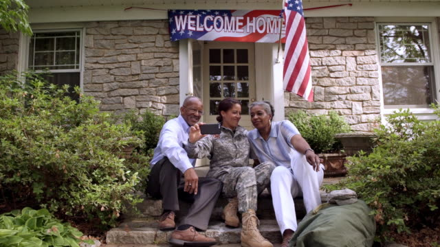 Parents and military daughter posing for cell phone selfie front stoop