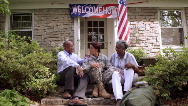 Parents and military daughter talking on front stoop