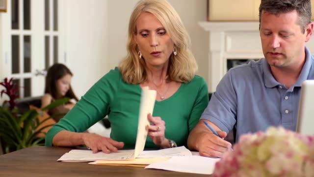 Eltern diskutieren Haushaltskosten mit Kindern im Hintergrund