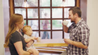 Parents Enjoy Coffee At Cafe With Baby