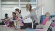 4K: Parents exercising with their babies in a gym.