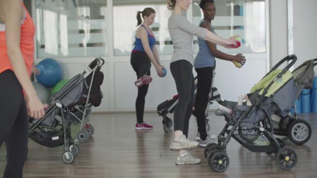 4 K : Genitori con i loro bambini esercizio con passeggini.