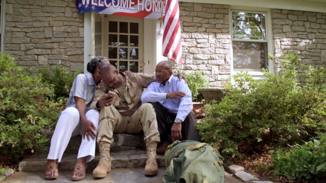 Parents hugging military son holding cell phone on front stoop