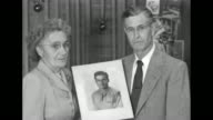 Parents of POW hold his photograph and pose for camera / SOT mother about son was reported missing last December received two letters husband...