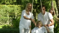 MS Parents playing with son (8-9) on swing in garden, Cape Town, South Africa