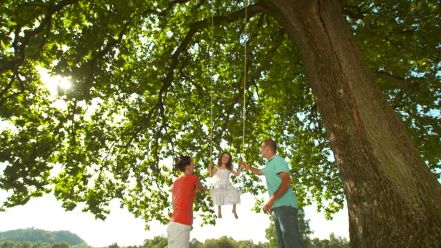 HD DOLLY: Parents Pushing Daughter On Swing