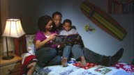 MS, ZI, CU, parents reading book to son (6-7) sitting on bed, Westfield, New Jersey, USA