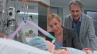 DS Parents talking to their daughter in the intensive care unit