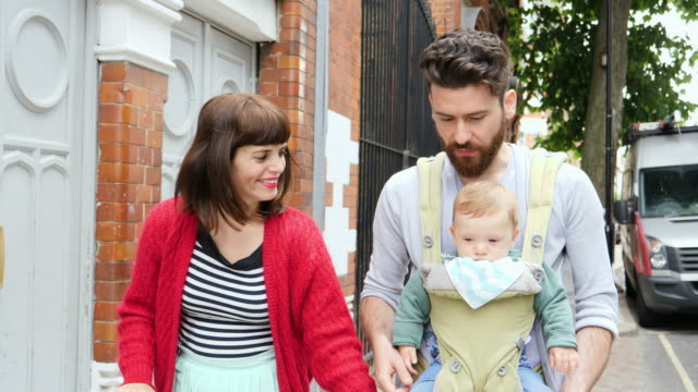 Parents walk with  baby son in baby carrier in urban street.