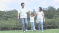 Parents walking hand in hand with daughter in park  and lifting her up