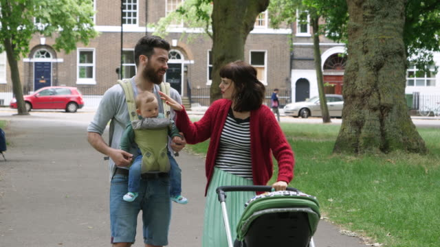 Parents walking with pram and baby son in baby carrier in park.