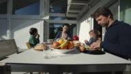 MS Parents with children (2-5) having breakfast on porch / Kleinmachnow, Brandenburg, Germany