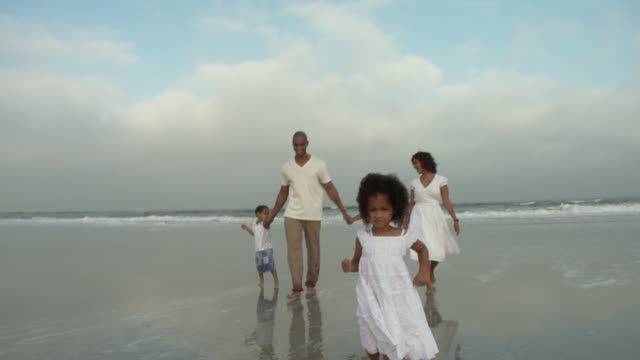 WS POV Parents with children (2-9) on beach, girl running in foreground / Jacksonville, Florida, USA