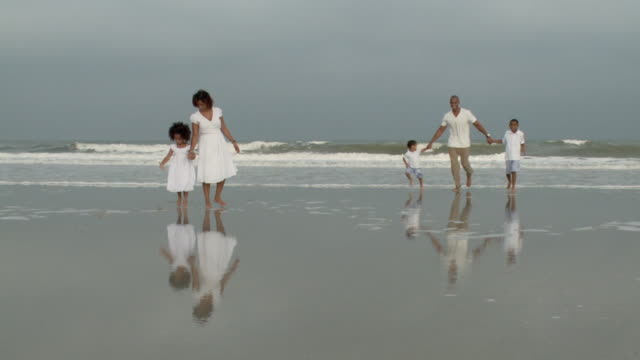 WS Parents with children (2-9) running from water at beach / Jacksonville, Florida, USA