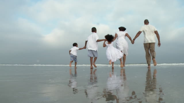 WS Parents with children (2-9) running in water on beach / Jacksonville, Florida, USA