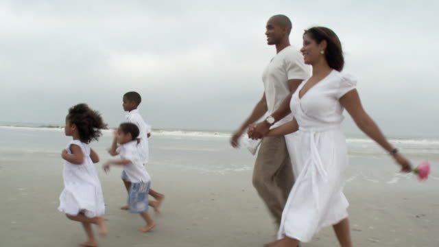 WS TS Parents with children (2-9) running on beach / Jacksonville, Florida, USA