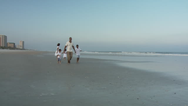 WS SLO MO Parents with children (2-9) running on beach / Jacksonville, Florida, USA