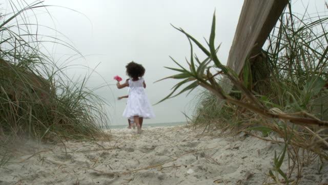 MS Parents with children (2-9) running towards beach through beach walkway / Jacksonville, Florida, USA