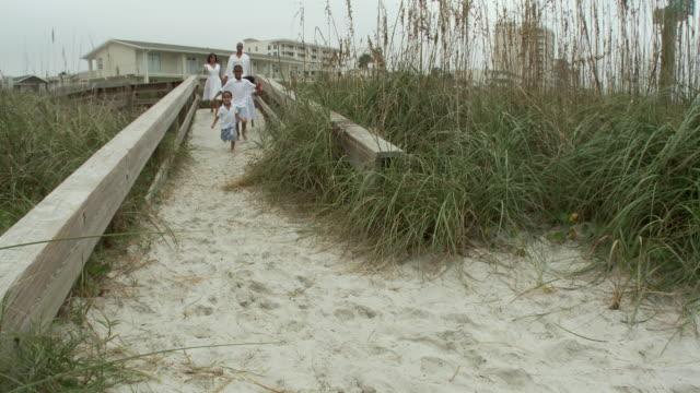 WS Parents with children (2-9) walking down walkway towards beach / Jacksonville, Florida, USA