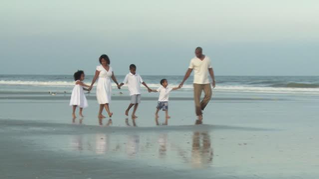 WS ZO Parents with children (2-9) walking on beach / Jacksonville, Florida, USA