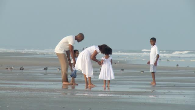 WS Parents with children (2-9) walking on beach / Jacksonville, Florida, USA
